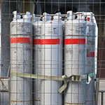 Tall metal gas canisters secured in wired cage
